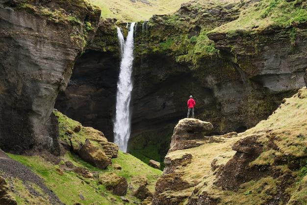 Kvernufoss-wasserfall in der schlucht, island. mann tourist in roter jacke schaut auf den strom des fallenden wassers