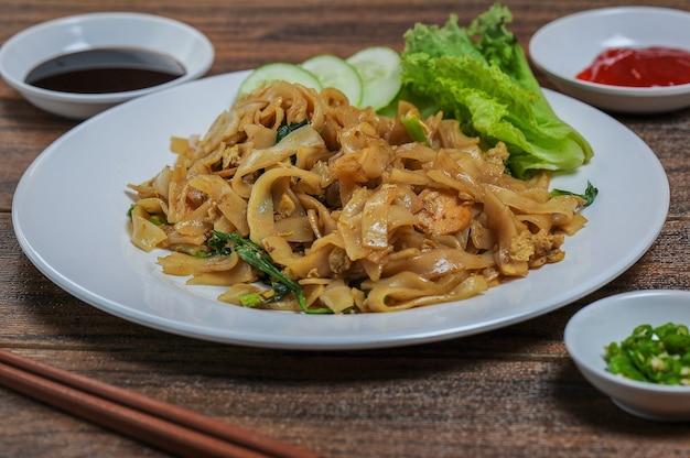 Kwetiau ist die chinesische küche, die in indonesien beliebt ist und durch frittieren mit beilagen zubereitet wird