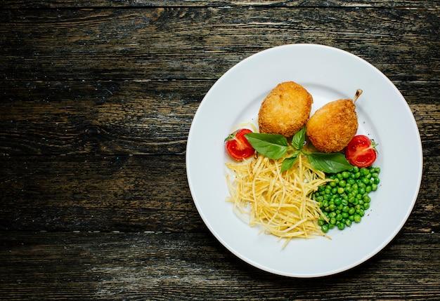 Kyev schnitzel mit knochen, grünen bohnen und nudeln