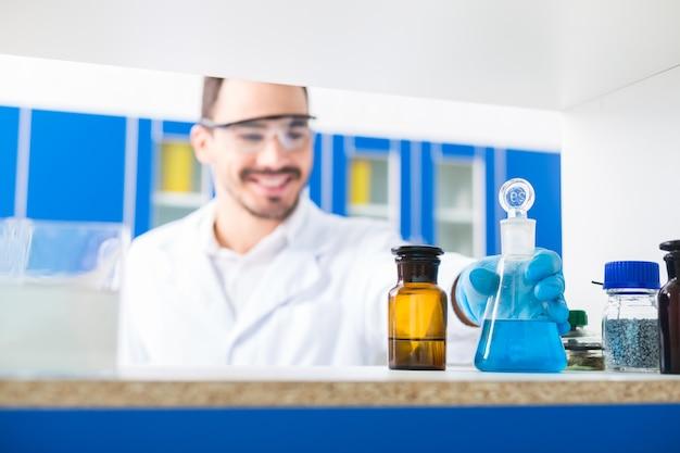 Labor drinnen. selektiver fokus der männlichen hand, die laborgläser mit eingegossenen flüssigkeiten nimmt und auf der oberfläche steht