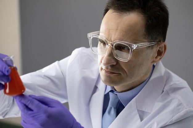 Laborant im chemielabor mit reaktionsröhrchen wissenschaftliche forschung