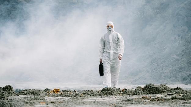 Laborantin in maske und chemikalienschutzanzug geht auf trockenem boden mit werkzeugkasten durch...