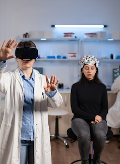 Laborarzt, der virtuelle realität mit vr-brille im medizinischen neurologischen forschungslabor erlebt. arzt mit brille für medizinische innovationsgeräte, analyse des gehirnscans.