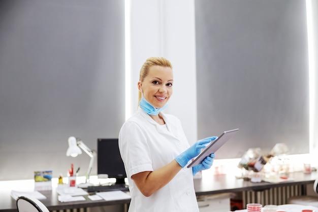 Laborassistent, der im labor steht und tablette verwendet, um testergebnisse einzugeben.