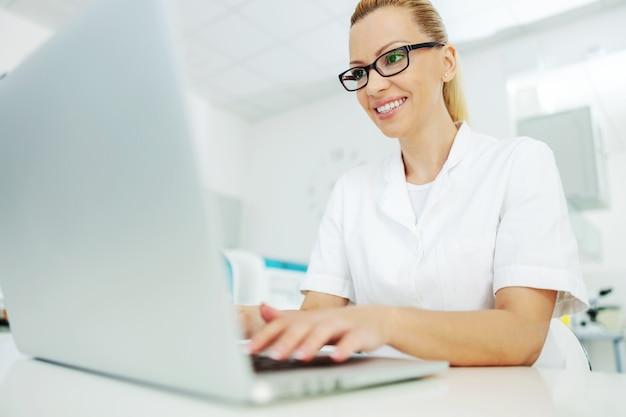 Laborassistent im mantel mit brille, die im labor sitzt und auf laptopbericht tippt.