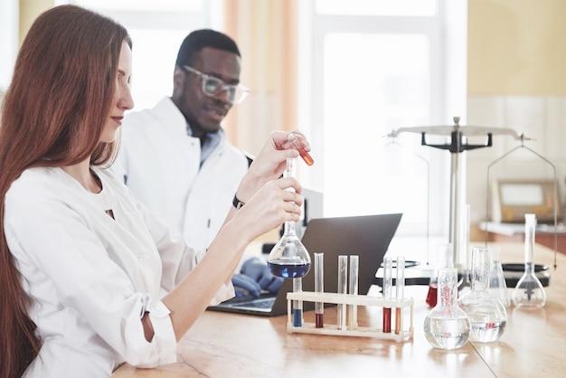Laboratorien führen experimente in einem chemischen labor in transparenten kolben durch. ausgabeformeln.