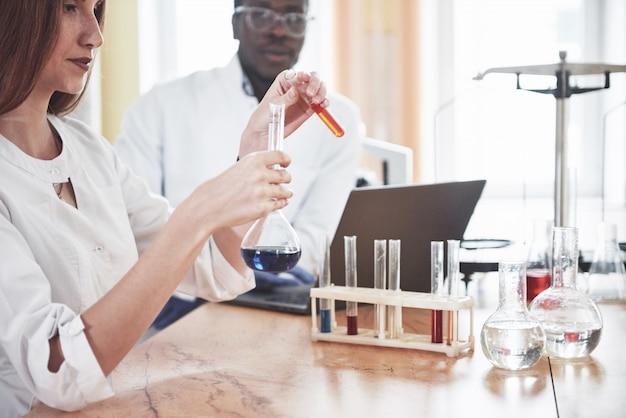 Laboratorien führen experimente in einem chemischen labor in transparenten kolben durch. ausgabeformeln