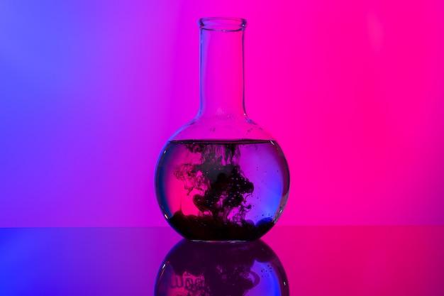 Laborglasgefäße mit chemikalien auf hellem rosa