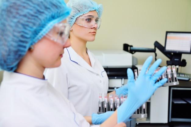 Labormädchen ziehen gummihandschuhe an