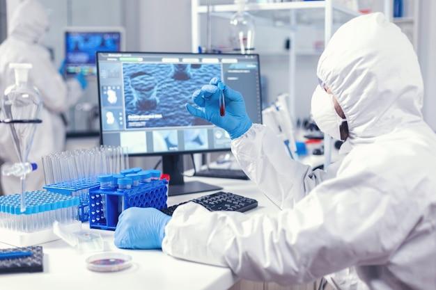 Labormitarbeiter, der testblut für den nachweis von coronavirus vorbereitet, der in ppe gekleidet ist. arzt, der mit verschiedenen bakterien und geweben arbeitet, pharmazeutische forschung für antibiotika gegen covid19.