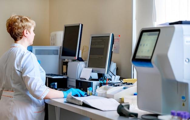 Labortechnikerfrau, welche die analyse des bluts, arbeitend an dem computer überprüft.
