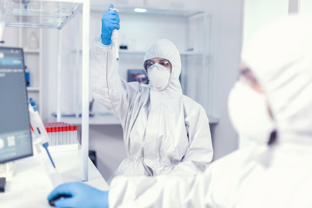 Laborwissenschaftler im gesundheitswesen, der eine mikropipette mit einer probe in einem ppe-anzug gegen coronavirus hält. team von mikrobiologen im forschungslabor, das experimente während der globalen pandemie durchführt