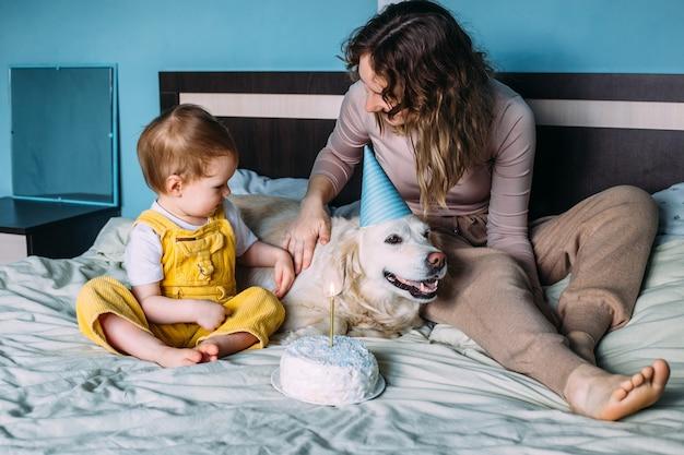 Labrador golden retriever mit kleinem kind feiern geburtstag mit kuchen