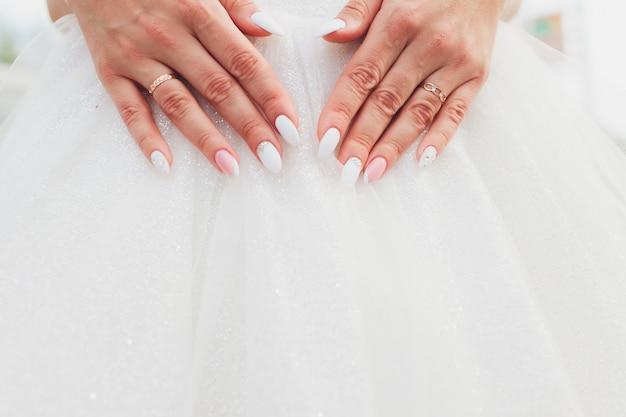 Lace weißes hochzeitskleid mit langen ärmeln. frauenhände.