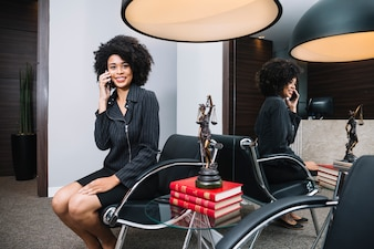 Lächelnde Afroamerikanerfrau, die auf Smartphone auf Lehnsessel im Büro spricht