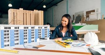 Lächelnde Afroamerikanerfrau nahe Modell des Gebäudes auf Tabelle mit Ausrüstungen