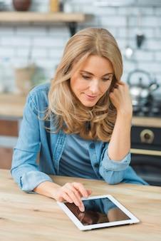 Lächelnde blonde junge Frau, die die empfindliche digitale Tablette der Note auf Tabelle verwendet