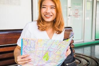 Lächelnde Frau mit Karte auf Bank