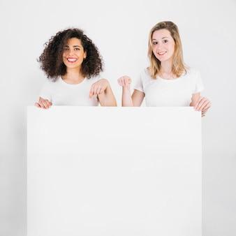 Lächelnde Frauen, die auf leeres Plakat zeigen