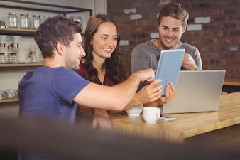 Lächelnde Freunde, die Tablet-Computer zeigen und betrachten