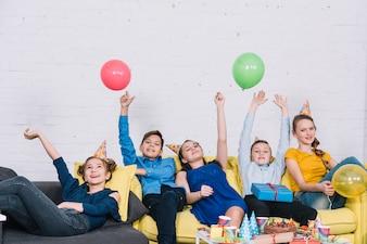 Lächelnde Freunde, die zu Hause die Geburtstagsfeier genießen