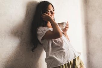 Lächelnde Jugendliche, die auf der Tapete hält Kaffeetasse sich lehnt