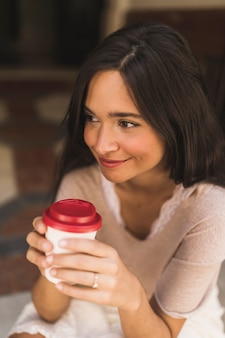 Lächelnde Jugendliche, die Kaffeetasse wegnehmen hält