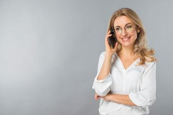 Lächelnde junge Frau, die am Handy gegen grauen Hintergrund spricht