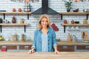 Lächelnde junge Frau, die hinter dem Holztisch in der Küche steht