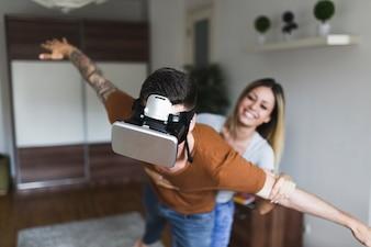 Lächelnde junge Frau, welche die Hand des Mannes tragender Kopfhörer der virtuellen Realität hält