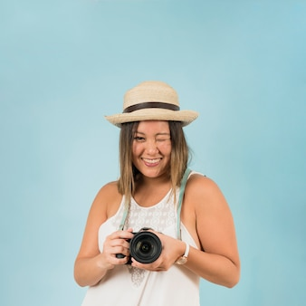 Lächelnde junge Frau, welche in der Hand die Kamera blinzelt gegen blauen Hintergrund hält