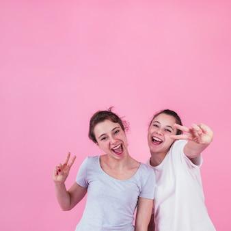 Lächelnde junge Frauen, die das Friedenszeichen steht gegen rosa Hintergrund zeigen