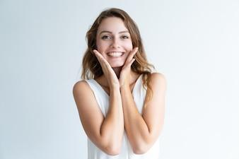 Lächelnde junge hübsche Frau, die Kamera und rührendes Gesicht betrachtet