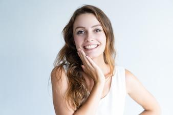 Lächelnde junge reizende Frau, die Kamera und rührendes Gesicht betrachtet