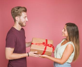 Lächelnde Paarholding wickelte Geschenkbox gegen rosa Hintergrund ein