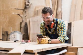 Lächelnde tragende Sicherheitsgläser und Ohrenschützer des männlichen Tischlers um seinen Hals unter Verwendung des Mobiltelefons
