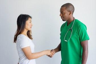 Lächelnder Doktor, der jungen weiblichen Patienten mit Händedruck grüßt.