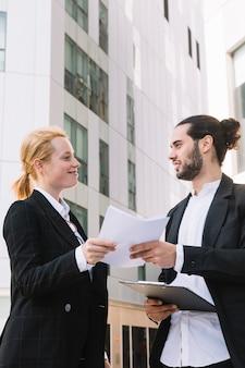 Lächelnder Geschäftsmann und Geschäftsfrau, die Schreibarbeit in den Händen an draußen hält