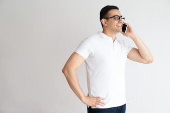 Lächelnder gutaussehender Mann, der am intelligenten Telefon spricht. Junger Mann, der um Mobiltelefon ersucht.