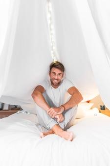 Lächelnder junger Mann, der auf Bett unter dem weißen Vorhang sitzt