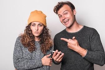 Lächelnder Mann, der Finger auf die kranke Frau hält Thermometer zeigt