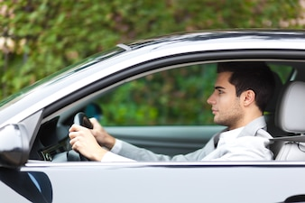 Lächelnder Mann, der sein Auto antreibt