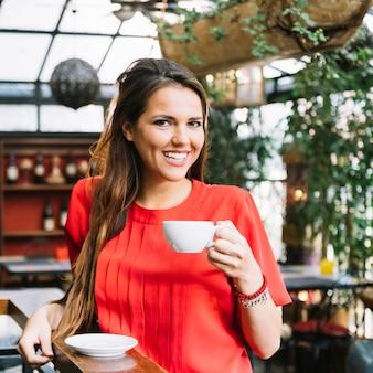 Lächelnder trinkender Tasse Kaffee der jungen Frau in cafÃ?