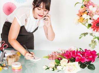 Lächelnder weiblicher Florist, der auf Mobiltelefon spricht und Anmerkungen auf Notizblock schreibt