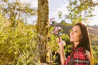 Lächelnder weiblicher Tourist, der Lupe vor Blumen hält