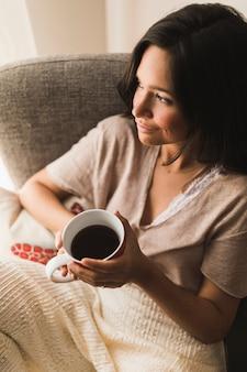 Lächelndes Mädchen, das Kaffeetasse in den Händen hält