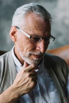 Lächelndes Porträt eines älteren Mannes mit der Hand auf seinem Kinn