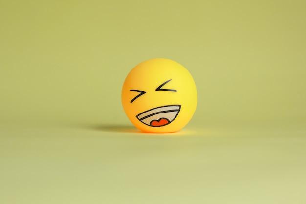 Lachen emoticon lokalisiert auf gelbem hintergrund