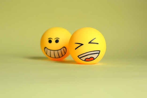 Lachen emoticon und verschwommenes smiley emoticon lokalisiert auf gelbem hintergrund
