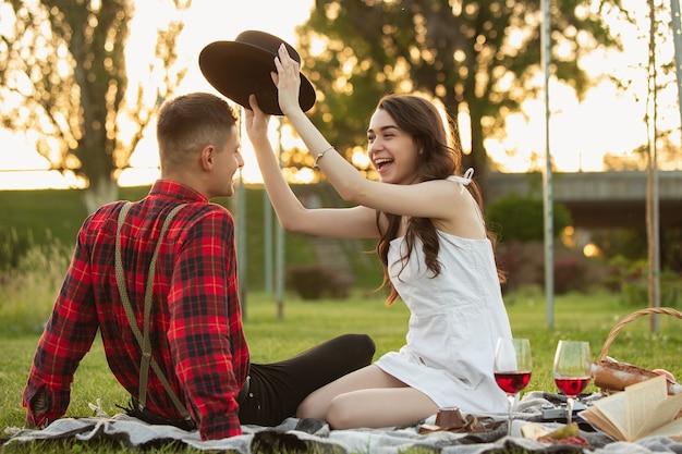 Lachen, lächeln. kaukasisches junges paar, das am sommertag zusammen ein wochenende im park genießt?